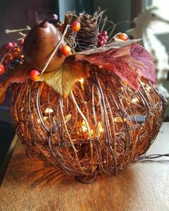 grapevine pumplin lit with mini lights and decorated on the top with fall follage and harvest minitures