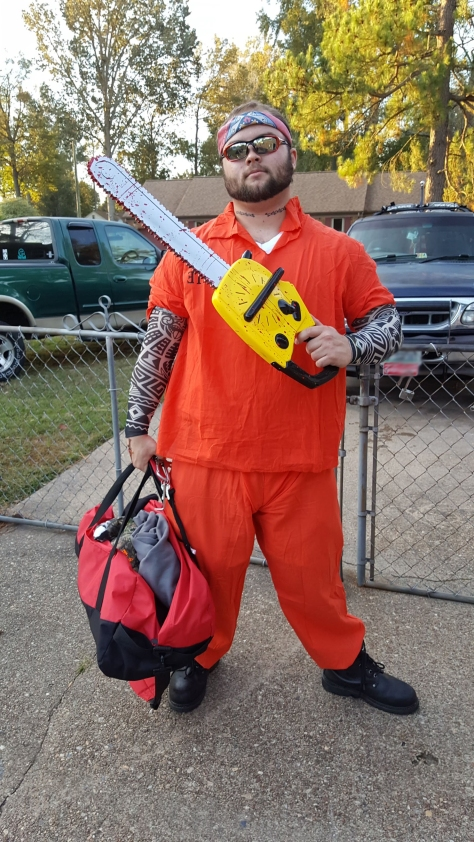 man dressed in orange confict jumpsuide holding toy chainsaw